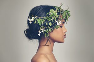 female model photographed in profile while wearing a hairpiece with twigs and flowers