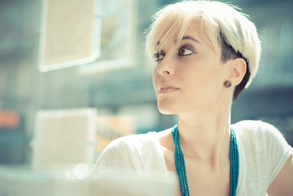 blonde model sitting near window with pixie cut